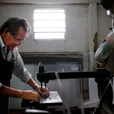 Diacízio Alves de Oliveira, 53 anos, casado, 2 filhos, 1 neto, micro-empresário.Chegamos logo cedo na AcriTraços, microempresa de Diacízio há 12 anos. É ele quem toca seu negócio, fazendo um pouco de tudo, desde o atendimento ao cliente até a produção das peças. Foi interessante conhecer seu ambiente de trabalho, que se assemelha ao de uma marcenaria. Ele nos apresenta todo o lugar: o escritório onde atende as ligações dos clientes e projeta as peças sob encomenda; a fábrica, onde cortam as placas de acrílico, lixam, constroem as peças. Uma sala, no andar de cima, está reservada para o silkscreen, quando necessário – algumas encomendas precisam ser personalizadas. Talvez a Acritraços seja vendida porque Diacízio irá transplantar em breve e precisará ficar em repouso durante um tempo. Como ele é o motor de lá, não sabe quem poderia continuar com seu negócio enquanto se recupera.De qualquer forma, ele está com grandes espectativas para o transplante. Há um ano e meio que faz a diálise peritoneal. Descobriu que era renal crônico quando fez alguns exames de rotina, em março de 2007. Em setembro começou a DP direto, sem passar por hemodiálise. Quando conversou com Dr. Luiz, soube dos dois métodos possíveis naquele momento – a hemodiálise e a diálise peritoneal. Optou pela segunda para continuar trabalhando e com suas atividades. Um dos motivos também que ressaltou é que na HD tem medo de pegar alguma infecção ou doença, já que a máquina se conecta a várias pessoas. Sua diálise peritoneal é um tanto curiosa. Dr. Luiz receitou uma combinação dos dois métodos – manual e automática – para que ele se adaptasse melhor ao tratamento. Sendo assim, Diacízio se conecta na máquina à noite, se desconecta de manhã e faz uma troca manual ao meio-dia.Seu transplante era para ter acontecido antes, mas como ele teve algumas complicações de saúde, não foi possível. A data deve ser marcada nos próximos meses, porém