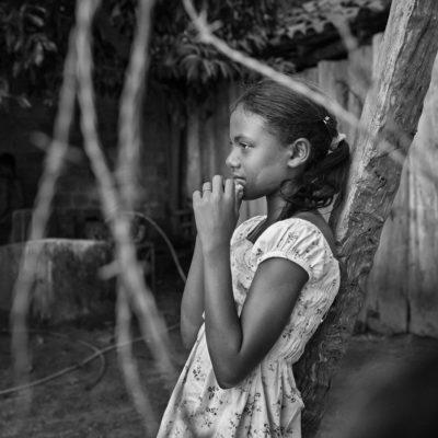Lauany Vitória do Carmo da Conceição, 10 anos, solteira, estudante, paciente de hanseníase diagnosticada pela Carreta de Saúde. Mãe: Marciane do Carmo da Conceição (16/11/85), 28 anos, casada, 5 filhos (grávida do 5o. filho), dona de casa. Seguimos de carro agora para a casa de Lauany Vitória do Carmo da Conceição , 10 anos, a menina que teve o diagnóstico de hanseníase na carreta. Falamos com sua mãe, Marciane, e com suas tias. As crianças brincam enquanto conversamos. Lauany é tímida, mas fala com a gente. Conta que gosta de brincar de bola e de dançar. As tias falam que ela ganha todas as competições de pancadão da cidade, que a menina rebola até o chão! Lauany se encosta em um tronco de árvore enquanto André fotografa. Com o olhar sereno, ela não se intimida com a câmera. Agradecemos a recepção da família e combinamos de voltar amanhã para fazer uma foto da menina na escola. A mãe, grávida do quinto filho, concorda e agradece a visita. Nos despedimos de Baixinho e seguimos viagem de volta até Araguaína.